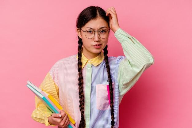 Молодая китайская студентка, держащая книги в модной разноцветной рубашке и тесьме, изолированная на розовом фоне, потрясена, она вспомнила важную встречу.