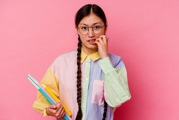 Молодая китайская студентка женщина, держащая книги в модной разноцветной рубашке и косе, изолированная на розовом фоне, кусающая ногти, нервная и очень взволнованная.