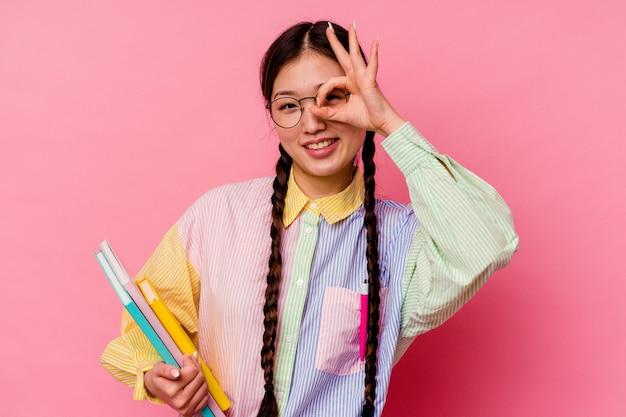 ピンクの背景で隔離されたファッションマルチカラーシャツとブレードを身に着けている本を保持している若い中国人学生の女性は、目に大丈夫なジェスチャーを維持して興奮しています。