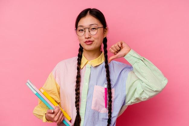 ピンクの背景に分離された、ファッションマルチカラーシャツとブレードを身に着けている本を持っている若い中国人学生の女性は、誇りと自信を感じています。