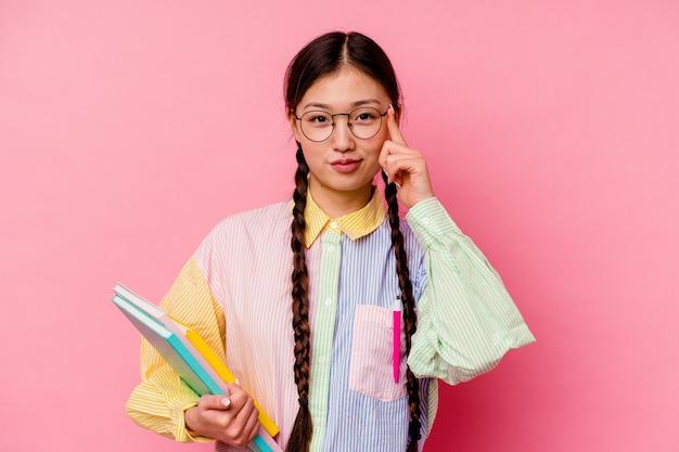 Молодая китайская студентка женщина, держащая книги в модной разноцветной рубашке и тесьме, изолированная на розовом фоне, указывая пальцем на храм, думает, сосредоточена на задаче.