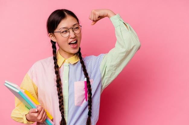 Молодая китайская студентка женщина, держащая книги в модной разноцветной рубашке и тесьме, изолированная на розовом фоне, поднимающая кулак после победы, концепции победителя.