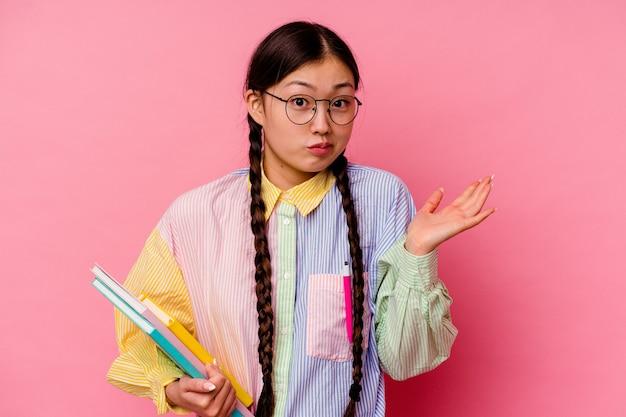 Молодая китайская студентка, держащая книги в модной разноцветной рубашке и тесьме, изолирована на розовом фоне, пожимает плечами и смущается открытыми глазами.