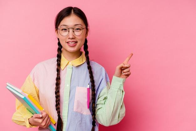 Молодая китайская студентка женщина, держащая книги в модной разноцветной рубашке и тесьме, изолированная на розовом фоне, улыбаясь и указывая в сторону, показывая что-то на пустом месте.