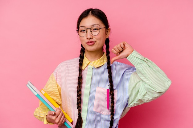 Young chinese student woman holding books wearing a fashion multicolour shirt and braid, isolated on pink background feels proud and self confident, example to follow.