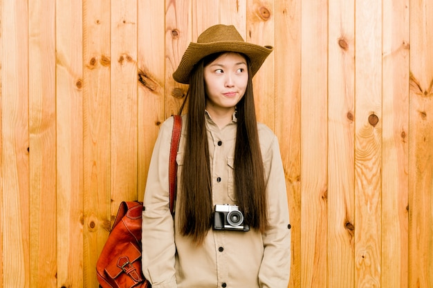 Young chinese traveler woman confused, feels doubtful and unsure.