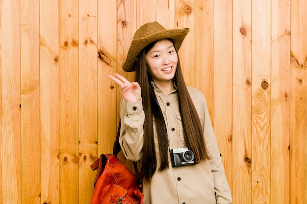 Young chinese traveler woman joyful and carefree showing a peace symbol with fingers.