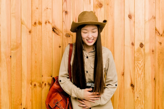 Young chinese traveler woman laughs happily and has fun keeping hands on stomach.