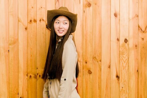 若い中国人旅行者の女性は笑みを浮かべて、陽気で楽しい脇に見えます。