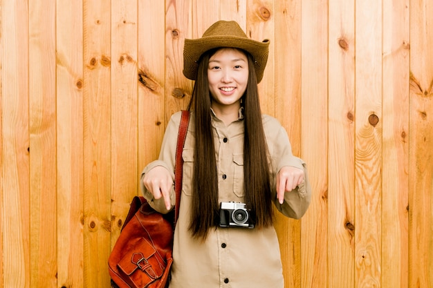 Young chinese traveler woman points down with fingers, positive feeling.