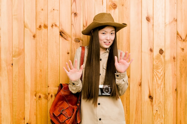 Young chinese traveler woman rejecting someone showing a gesture of disgust.