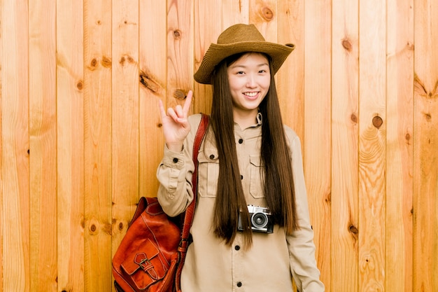Young chinese traveler woman showing a horns gesture as a revolution concept.