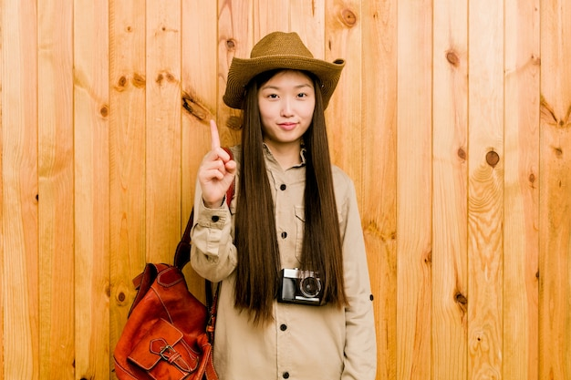 Young chinese traveler woman showing number one with finger.