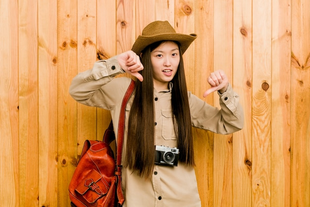 Young chinese traveler woman showing thumb down and expressing dislike