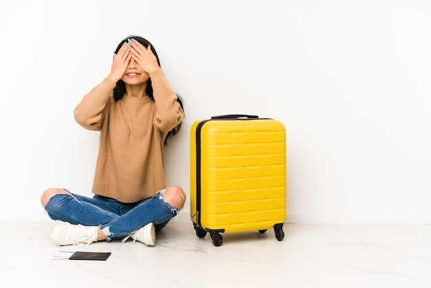 Young chinese traveler woman siting on the floor with a suitcase isolated covers eyes with hands, smiles broadly waiting for a surprise.