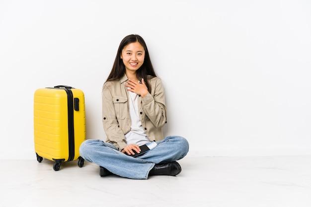 탑승권을 들고 앉아있는 젊은 중국 여행자 여자가 큰 소리로 가슴에 손을 유지하면서 웃음