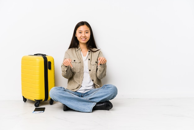 Молодая китайская женщина путешественника сидя держащ посадочные талоны указывает вниз с пальцами