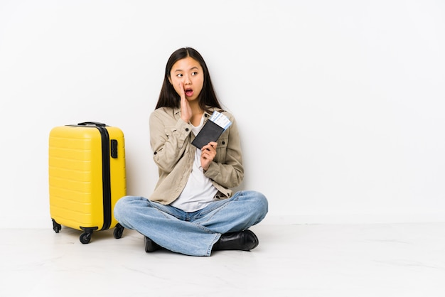Young chinese traveler woman sitting holding a boarding passes is saying a secret and looking aside