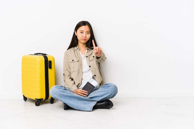Young chinese traveler woman sitting holding a boarding passes showing number one with finger.