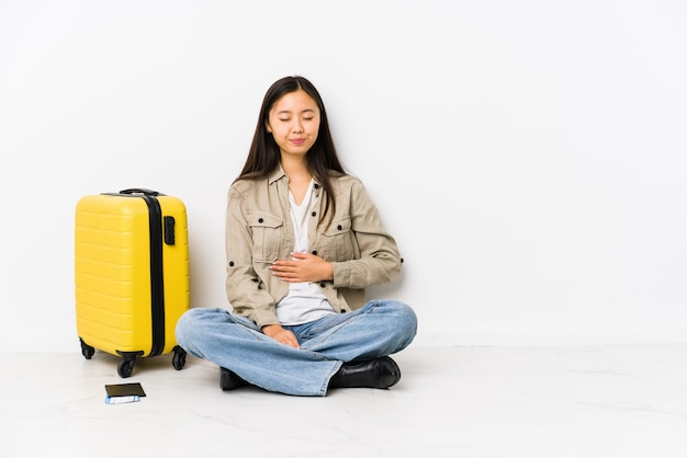 Young chinese traveler woman sitting holding a boarding passes touches tummy, smiles gently, eating and satisfaction concept.