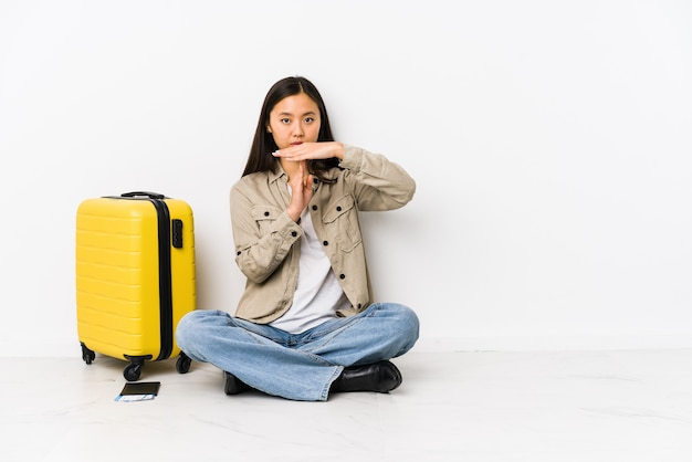 Young chinese traveler woman sitting holding a boarding passes