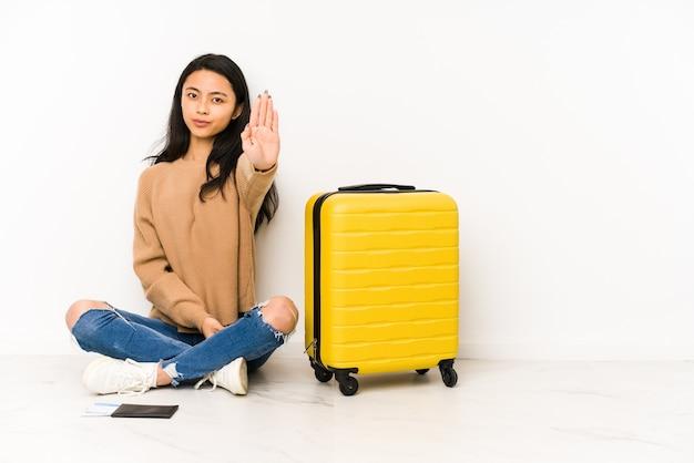 孤立した立っているスーツケースと床に座っている若い中国人旅行者の女性