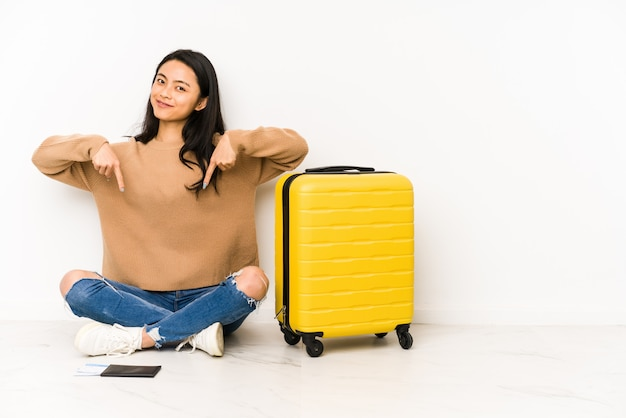 Young chinese traveler woman sittting on the floor with a suitcase points down with fingers