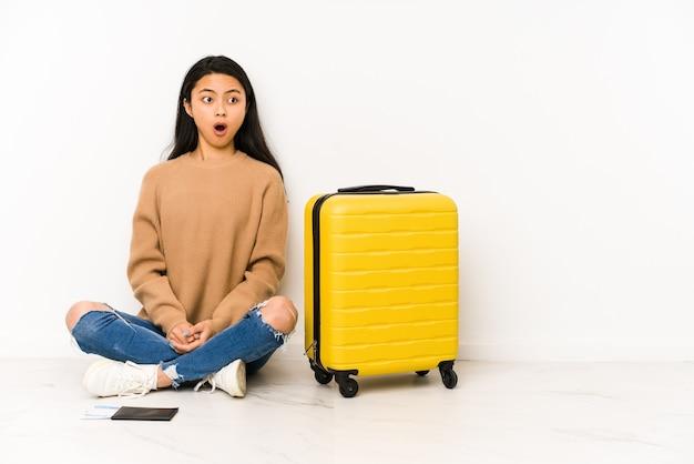 彼女が見た何かのためにショックを受けて孤立したスーツケースで床に座っている若い中国人旅行者の女性