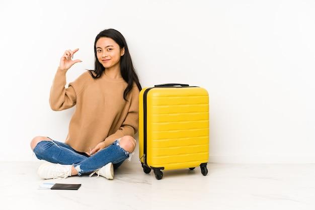 若い中国人旅行者の女性は、スーツケースを持って床に座って、人差し指で少し何かを持って、笑顔で自信を持っています。