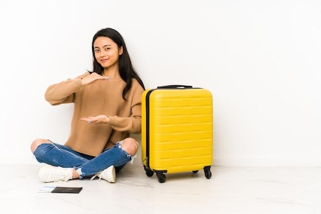 両手で何かを持って孤立したスーツケースを持って床に座っている若い中国人旅行者の女性、製品のプレゼンテーション。