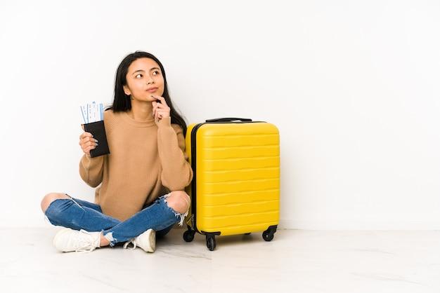 疑わしいと懐疑的な表情で横向きに孤立したスーツケースを持って床に座っている若い中国人旅行者の女性。