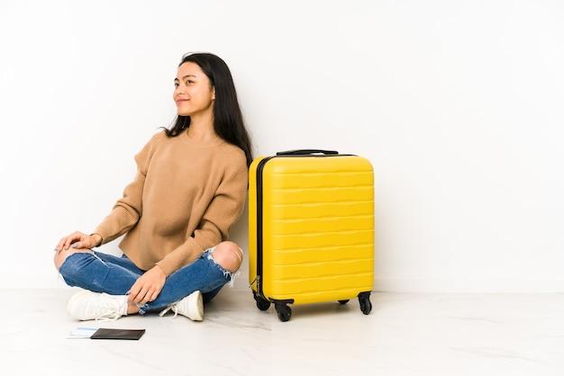 孤立したスーツケースを持って床に座っている若い中国人旅行者の女性は、笑顔、陽気で楽しい脇に見えます