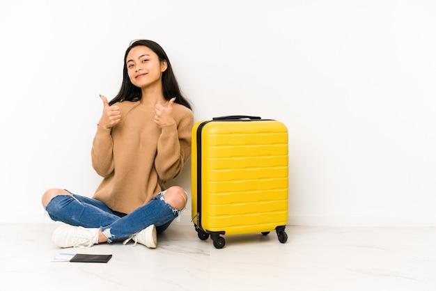 分離されたスーツケースを床に座っている若い中国人旅行者の女性が親指を上げて、笑顔で自信を持って。