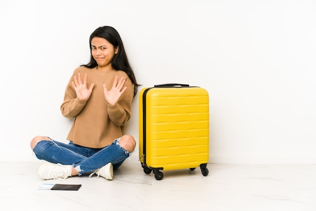 Молодой китайский путешественник женщина сидит на полу с изолированным чемоданом, отвергая кого-то, показывая жест отвращения.
