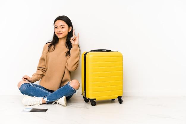 革命の概念として角のジェスチャーを示す孤立したスーツケースと床に座っている若い中国人旅行者の女性。