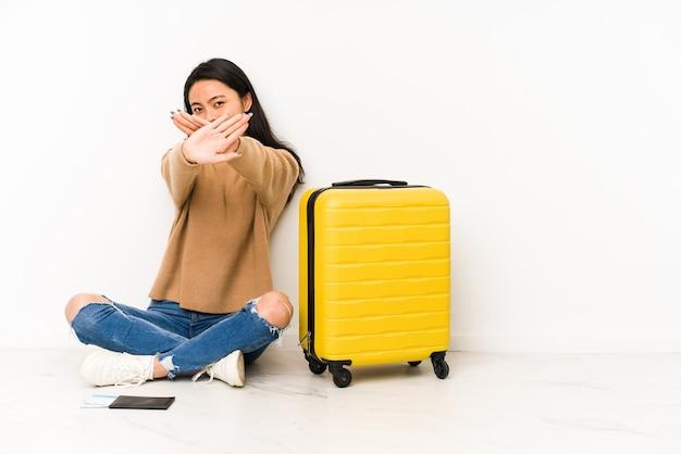 スーツケースと床に座っている若い中国人旅行者の女性