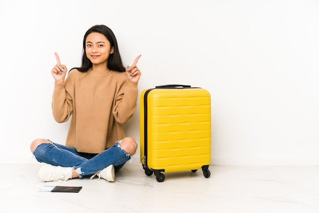 孤立したスーツケースを持って床の上に座っている若い中国人旅行者の女性は、両方の前指が空白を示していることを示しています。