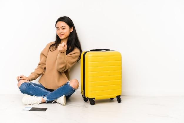 誘うようにあなたに指を指して孤立したスーツケースを持って床に座っている若い中国人旅行者の女性が近づいています。