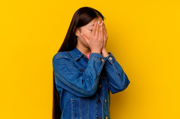 Young chinese woman  afraid covering eyes with hands.