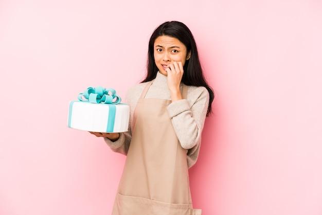 ケーキを持っている若い中国人女性は、開いた口の近くで叫び、手のひらを持って孤立しました。