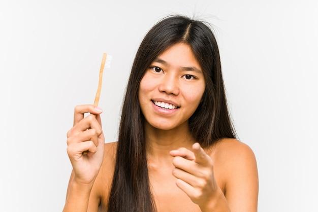 歯磨き粉を持っている若い中国人女性は、正面を指している陽気な笑顔を分離しました。