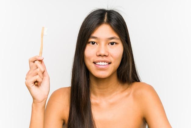 歯ブラシを保持している若い中国人女性は幸せ、笑顔、陽気を分離しました。