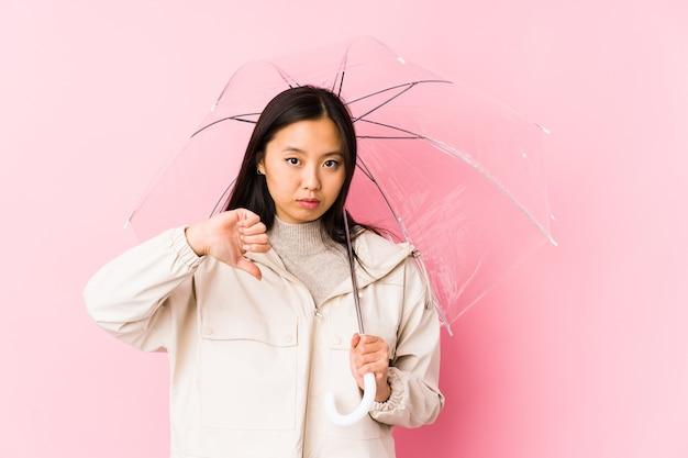우산을 들고 젊은 중국 여자는 싫어하는 제스처를 보여주는 절연 엄지 손가락. 불일치 개념.