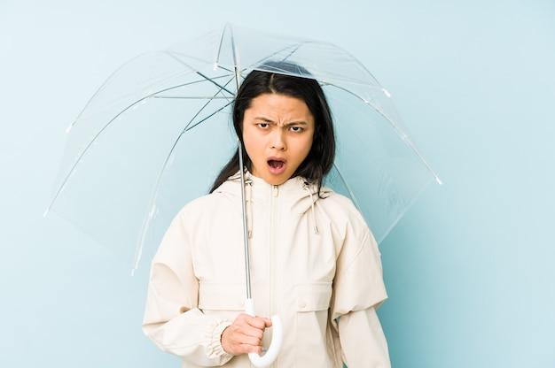 Молодая китаянка, держащая зонтик, изолировала радостную и беззаботную, показывая пальцами символ мира.
