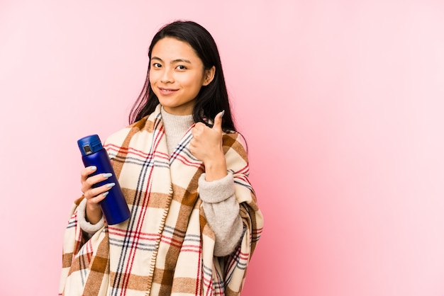 Young chinese woman holding a bottle and pointing aside, showing something at blank space.