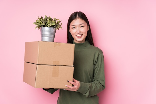 Young chinese woman holding boxes isolated happy, smiling and cheerful.