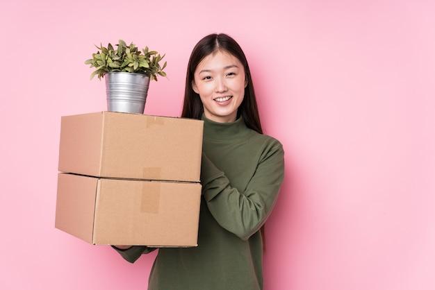 箱を持っている若い中国人女性は笑って楽しんで孤立しました。