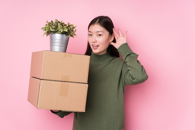 Young chinese woman holding boxes isolated trying to listening a gossip.