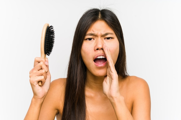 Young chinese woman holding a hairbrush isolated shouting excited to front.