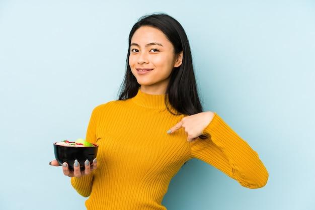 Молодая китаянка держит лапшу изолированно, мечтает о достижении целей и задач